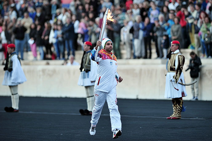 The last torch bearer, Greek figure skater Panagiotis Markouizos (C), brings the Olympic flame on October 5, 2013 into the Panathenaic stadium in Athens. (AFP Photo / Louisa Gouliamaki)