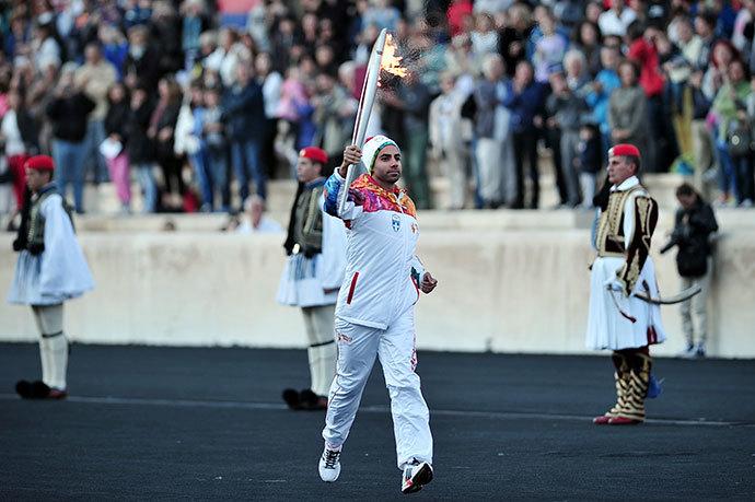 The last torch bearer, Greek figure skater Panagiotis Markouizos (C), brings the Olympic flame on October 5, 2013 into the Panathenaic stadium in Athens. (AFP Photo / Louisa Gouliamaki)