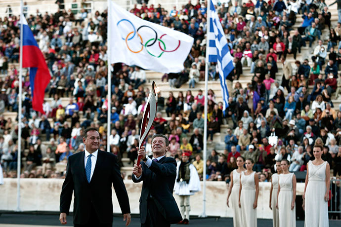 Russia's Deputy Prime Minister Dmitry Kozak (C) raises an Olympic torch for the Sochi 2014 Winter Games next to President of the Greek Olympic Committee Spyros Kapralos during a handover ceremony at the Panathenean stadium in Athens October 5, 2013.(Reuters / Yorgos Karahalis)