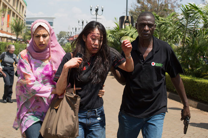 An injured woman (C) is helped out of the Westgate Shopping Centre where gunmen went on a shooting spree, in Nairobi September 21, 2013.(Reuters / Siegfried Modola)