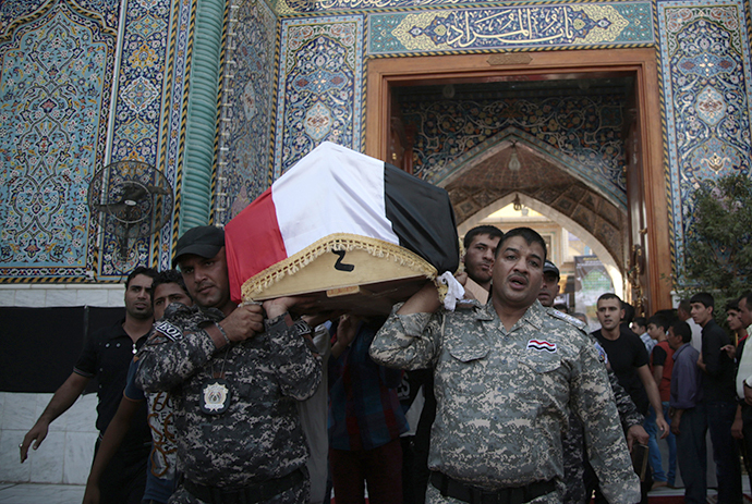 Mourners carry the coffin of a victim was killed by suicide bombers during a funeral at holy city of Kadhimiya in Baghdad October 6, 2013. (Reuters / Ahmad Mousa)
