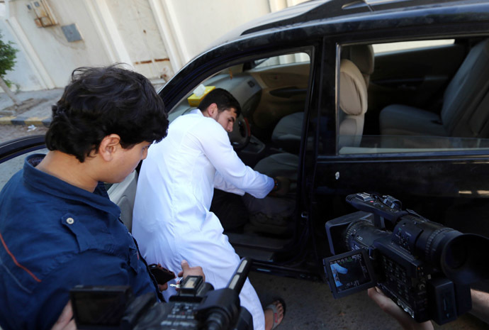 Abdullah al-Raghie (CL) and Abdul Moheman al-Raghie (L), the sons of al-Qaeda suspect Abu Anas al-Libi, show members of the press their father's car from which he was taken by US special forces in a commando raid in Nofliene, five kilometres from the Libyan capital Tripoli on October 6, 2013, sealing a 15-year manhunt for him. (AFP Photo)