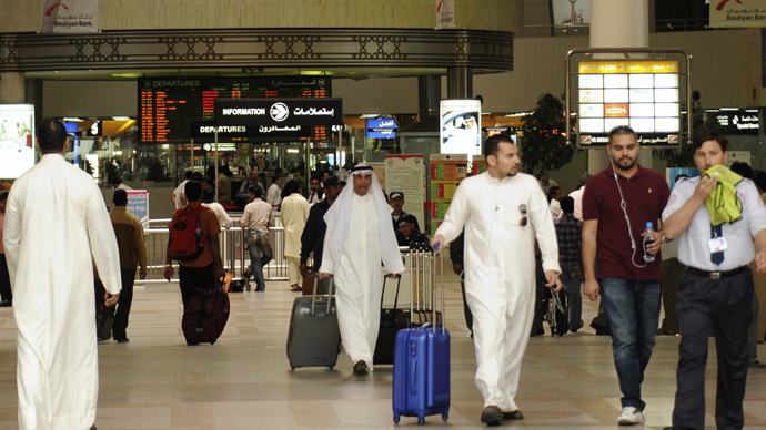 Travellers walk with their luggage at Kuwait International airport (Reuters/Stephanie McGehee)