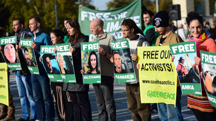 "Greenpeace supporters protest with placards reading ""free our activists"" against the detainment of Greenpeace activists by Russia at the Heroes square of Budapest on October 5, 2013.(AFP Photo / Attila Kisbenedek)"