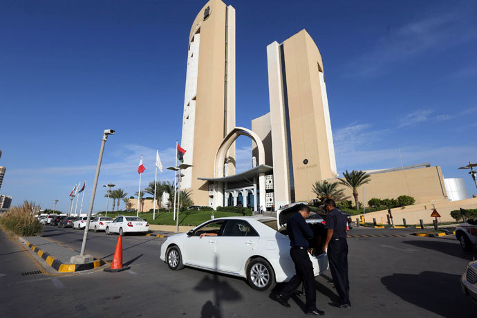 A general view taken on October 10, 2013 shows security checking a vehicle outside the Corinthia hotel (background) in the Libyan capital Tripoli after Libyan Prime Minister Ali Zeidan was kidnapped from the hotel, where he resides. (AFP Photo / Mahmud Turkia)