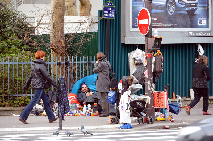 A homeless man talks to a pedestrian in the 14th district of Paris (AFP Photo / Miguel Medina)