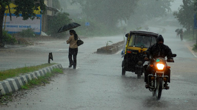 Indian residents make their way home through heavy cyclone rain in Berhampur city, about 180 kilometers south from eastern city Bhubaneswar on October 12, 2013. (AFP Photo / Asit Kumar)