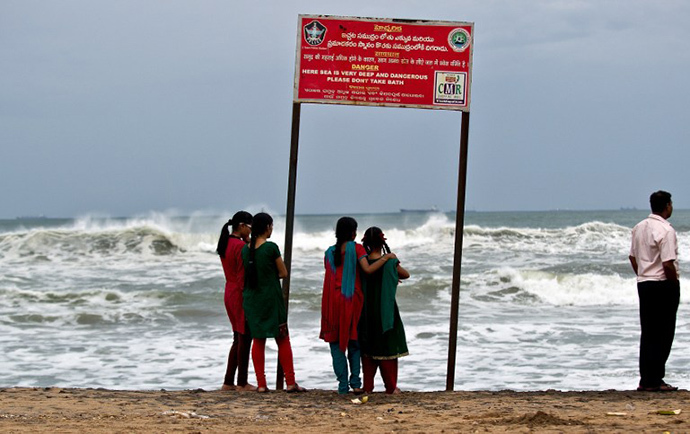 A group of Indian girls watch high tidal waves on the beach in Visakhapatnam on October 12, 2013. (AFP Photo / Manan Vatsyayana)