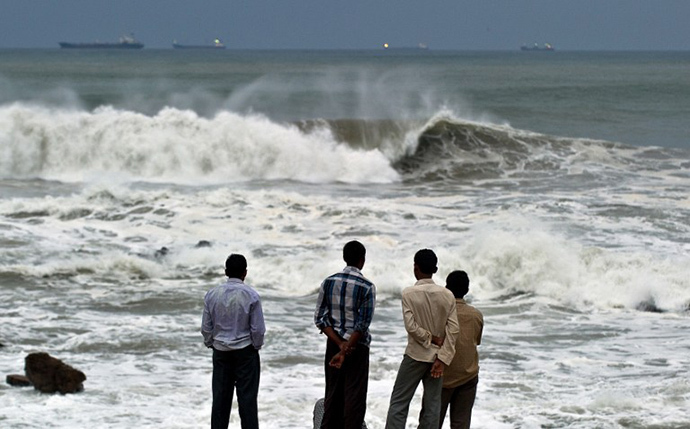 Indian youth stand on the shore as high tidal waves hit the coastline in Visakhapatnam on October 12, 2013. (AFP Photo / Manan Vatsyayana)