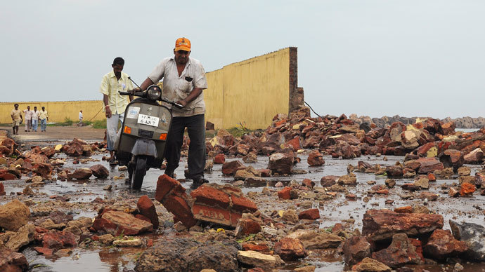 People walk among debris from a broken wall after it was damaged by a wave brought by Cyclone Phailin at a fishing harbour in Visakhapatnam district in the southern Indian state of Andhra Pradesh October 12, 2013. (Reuters / R Narendra)