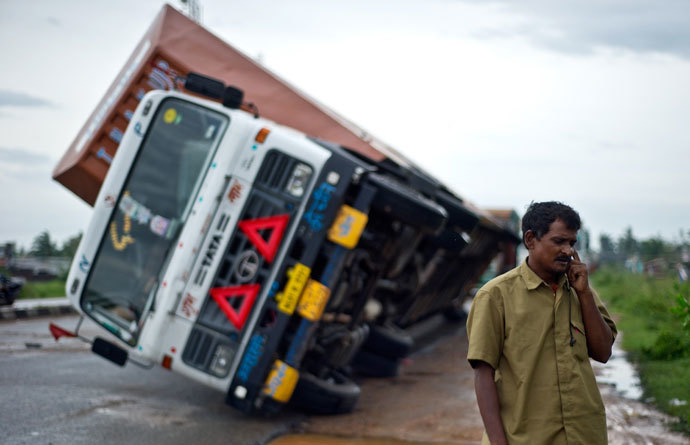 Indian truck driver Jairam Yadav speaks on his mobile phone after his truck carrying Toyota cars was overturned by strong wind on the National Highway linking Andhra Pradesh and Odisha on October 13, 2013.(AFP Photo / Manan Vatsyayana)