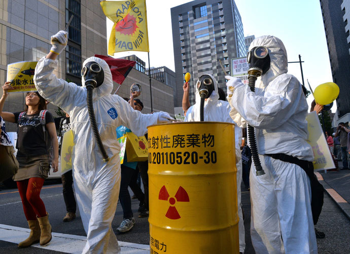 Protestors in radiation protection suits bang a drum can during an anti nuclear demonstration in front of the headquarters of the Tokyo Electric Power Co (TEPCO) in Tokyo on October 13, 2013.(AFP Photo / Yoshikazu Tsuno)
