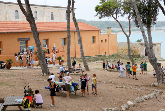 Tourists rest outside a hotel managed by the San Giacomo cooperative, on the Italian island of Pianosa on August 7, 2012.(AFP Photo / Fabio Muzzi)