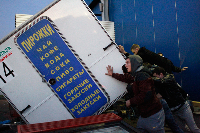 People turn over a kiosk in a vegetable warehouse in the Biryulyovo district of Moscow October 13, 2013 (Reuters / Maxim Shemetov)