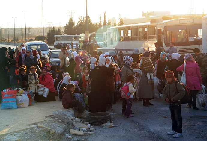 A handout picture released by the official Syrian Arab News Agency (SANA) on October 12, 2013 shows Syrian women and children waiting before being evacuated by Syria's Red Crescent from a Damascus suburb that has been under siege by the Syrian army for months. (AFP Photo)