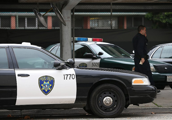 An Oakland Police officer walks by patrol cars at the Oakland Police headquarters (AFP Photo / Getty Images / Justin Sullivan)