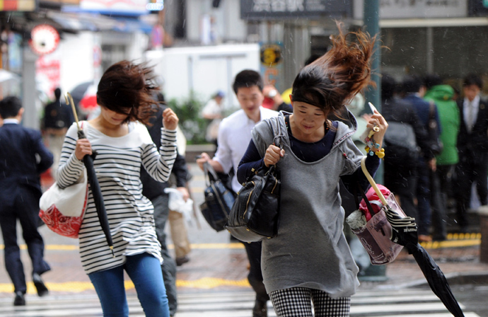 People walk against strong wind and rain in Tokyo on October 16, 2013 (AFP Photo / Yoshikazu Tsuno)
