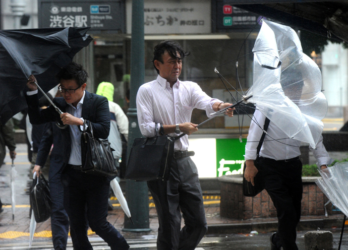 Japanese businessmen walk against strong wind and rain in Tokyo on October 16, 2013 (AFP Photo / Yoshikazu Tsuno)