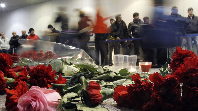 People walk past flowers left on a floor in memory of those killed in Monday's blast at Moscow's Domodedovo airport January 25, 2011. (Reuters/Denis Sinyakov)