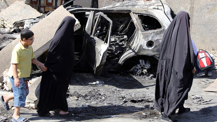 Iraqi women wlak past a burnt-out vehicle on October 7, 2013 following a bombing attack in Baghdad's eastern al-Jadidah district the night before. (AFP Photo / Ahmad al-Rubaye)