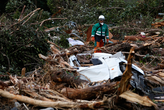 A rescue worker looks for a victim of a landslide caused by Typhoon Wipha in Izu Oshima island, south of Tokyo October 17, 2013 (Reuters / Yuya Shino)