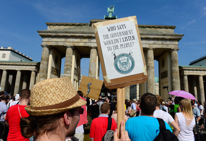 Demonstrators hold up banners as they take part in a protest in front of Berlin's landmark Brandenburg Gate against the US National Security Agency (NSA) collecting German emails, online chats and phone calls and sharing some of it with the country's intelligence services in Berlin on July 27, 2013 (AFP Photo/John Macdougall)