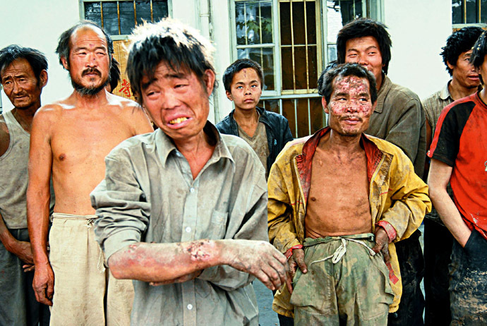 "A group of rescued workers stand outside a police station after they were saved from a brick kiln in Linfen, northern China's Shanxi province 27 May 2007. Police said 14 June that they had rescued more than 200 people, including 29 children, who were working as ""slaves"" in brick kilns, in a shocking revelation of labour practices in booming China. (AFP Photo)"