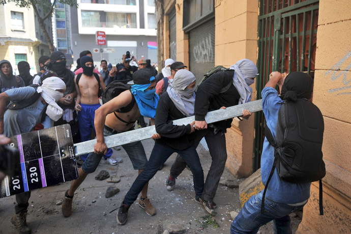 Demonstrators try to knock down the door of a house where there are policemen inside during a protest of sutudents demanding to Chilean President Sebastian Pinera's government to improve the public education quality, in Santiago, on October 17, 2013. (AFP Photo/Hector Retamal)