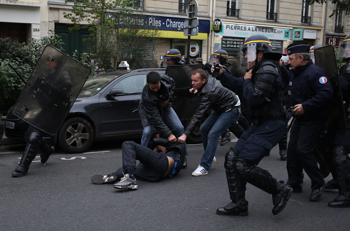 Anti riot police officers arrest a man as high school students demonste in Paris, on October 18, 2013, in protest against the deportation of foreign pupils following the high-profile eviction of a 15-year-old Roma girl (AFP Photo / Kenzo Tribouillard)