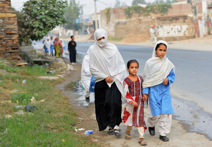 Pakistani schoolgirls walk along a path after school in Mingora, a town in Swat valley (AFP Photo / A Majeed)