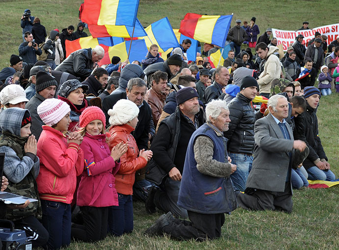 Protesters knee to pray during an anti shale gas exploration protest in Silistea village, on October 19, 2013. (AFP Photo / Adrian Arnautu)