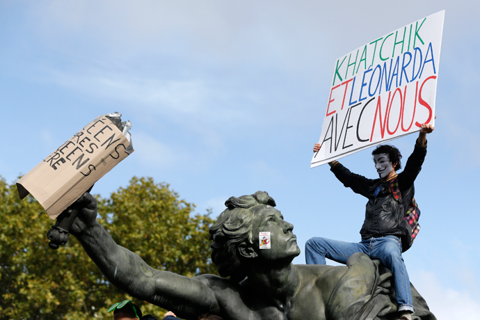"A man holds a sign which reads ""Khatchik and Leonarda with us"" as he stands on the statue at the Place de la Nation during a protest demonstration with French high school students in Paris October 18, 2013 (Reuters / Gonzalo Fuentes)"