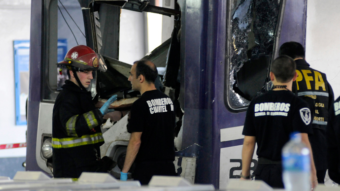 Picture released by NA showing firefighters inspecting the commuter train that apparently failed to stop and crashed at the end of the line at the Once railway terminal in Buenos Aires, on October 19, 2013 (AFP Photo / Hugo Villabos)