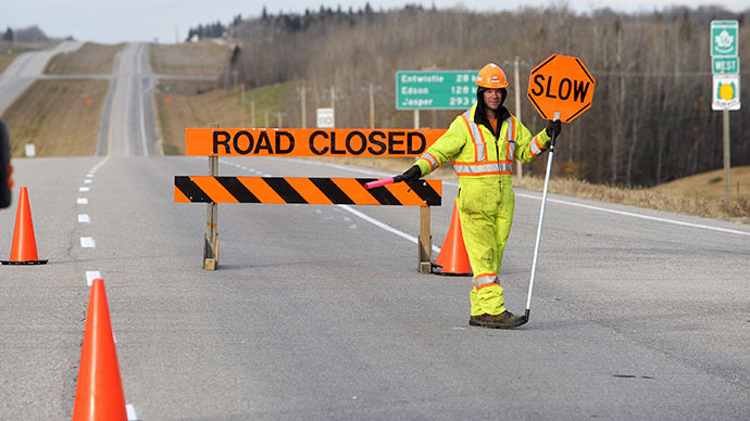 A Parkland County employee blocks a highway leading to an area where a train derailed, in the small town of Gainford, Alberta west of Edmonton October 19, 2013. (Reuters / Dan Riedlhuber)
