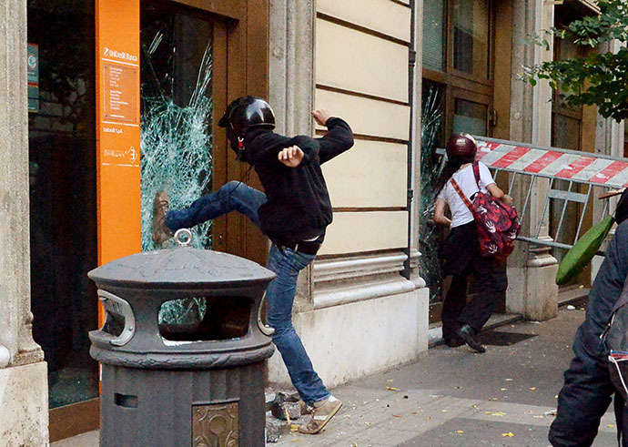 People try to broke the windows of an Unicredit bank agency during an anti-austerity protest on October 19, 2013 in Rome. (AFP Photo / Alberto Pizzoli)