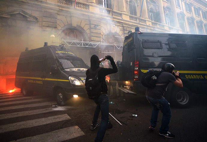 A man throws a bottle in direction of policem during clashes on the sidelines of an anti-austerity protest on October 19, 2013 in Rome. (AFP Photo / Filippo Monteforte)