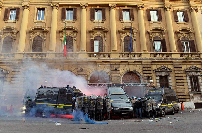 Members of the Guardia di Finanza protect themselves as they stand in front of the Economy minister during clashes on the sidelines of an anti-austerity protest on October 19, 2013 in Rome. (AFP Photo / Alberto Pizzoli)