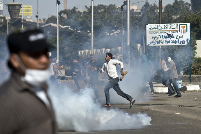 Egyptian students of al-Azhar university run for cover from a tear gas canister fired by riot police during clashes outside their university campus in Cairo on October 20, 2013 following an anti-army protest (AFP Photo / Khaled Desouki)