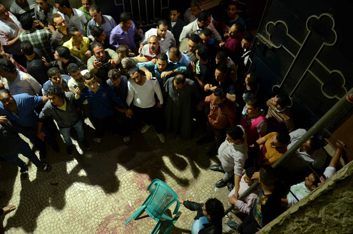 Egyptians gather around blood stains at the entrance of the Virgin Mary Coptic Christian church in Cairo after gunmen on a motorbike shot dead three people late on October 20, 2013, including an eight-year-old girl, in a shooting attack on a group standing outside the church in the Egyptian capital's Al-Warak neighbourhood following a wedding ceremony. (AFP Photo)