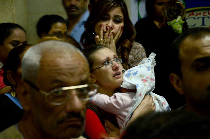 Egyptian women, some in tears, gather inside the Virgin Mary Coptic Christian church in Cairo after gunmen on a motorbike shot dead three people late on October 20, 2013, including an eight-year-old girl, in a shooting attack on a group standing outside the church in the Egyptian capital's Al-Warak neighbourhood following a wedding ceremony. (AFP Photo)
