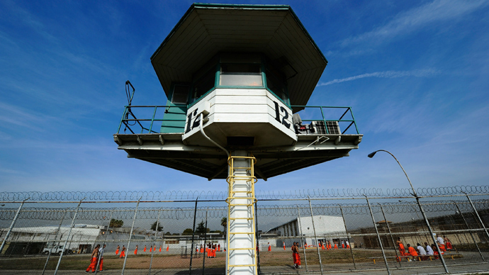 California Department of Corrections officer looks on as inmates at Chino State Prison exercise in the yard (AFP Photo)