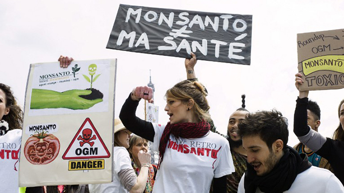 "People hold signs during one of many worldwide ""March Against Monsanto"" protests against GMOs and agro-chemicals (AFP Photo / Fred Dufour)"