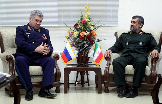 The head of the aerospace forces of the Iran's Revolutionary Guards, General Amir Ali Hajizadeh (R) and the head of the Russian Air Force, General viktor Bondarev (C) in Tehran on October 21, 2013 (AFP Photo)
