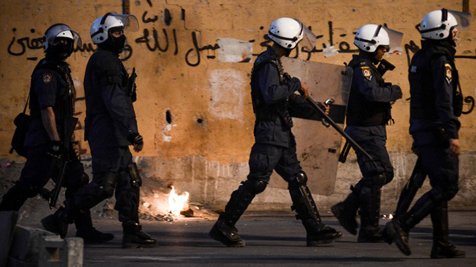 Bahraini riot policemen try to chase anti-regime protesters during clashes following the funeral of Ali Khalil Sabbagh in the village of Bani Jamrah, west of Manama, on October 23, 2013. (AFP Photo / Mohammed al-Shaikh)