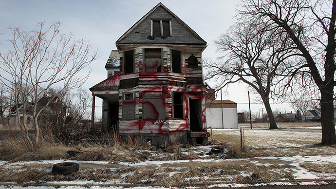 A vacant and blighted home, covered with red spray paint, sits alone in an east side neighborhood once full of homes in Detroit (Reuters / Rebecca Cook)