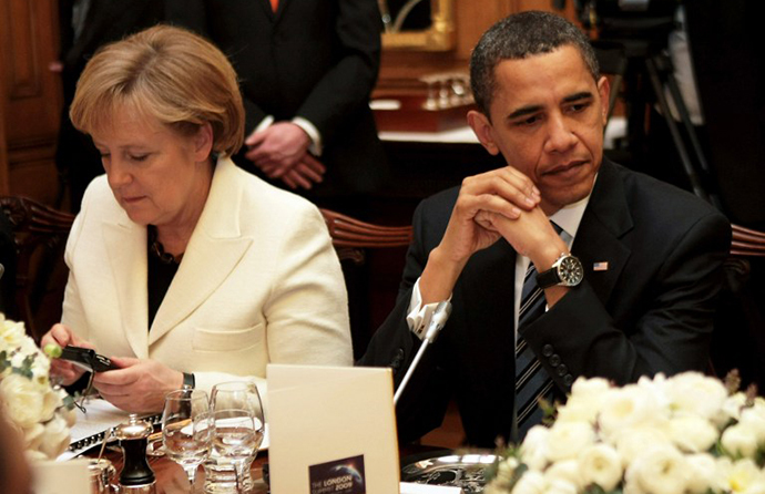 German Chancellor Angela Merkel looking at an electronic device as she sits next to US President Barack Obama (AFP Photo / Christopher Furlong)