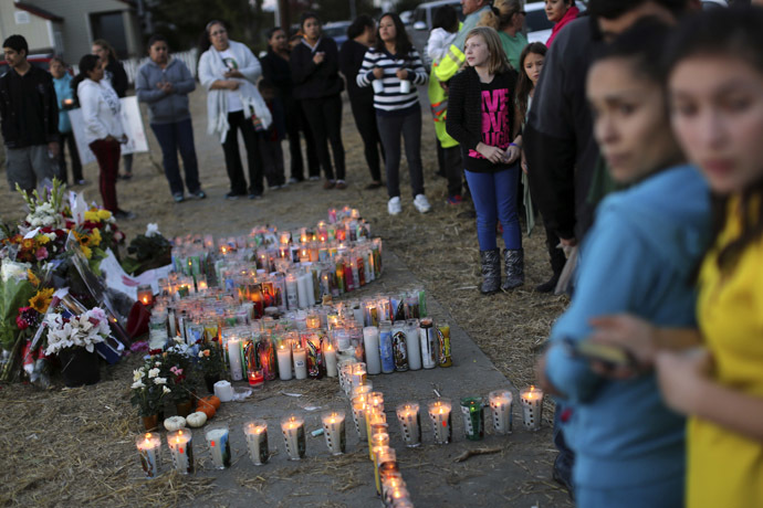 People look over a makeshift memorial for Andy Lopez Cruz at the site of his death in Santa Rosa, California October 24, 2013. (Reuters/Robert Galbraith)