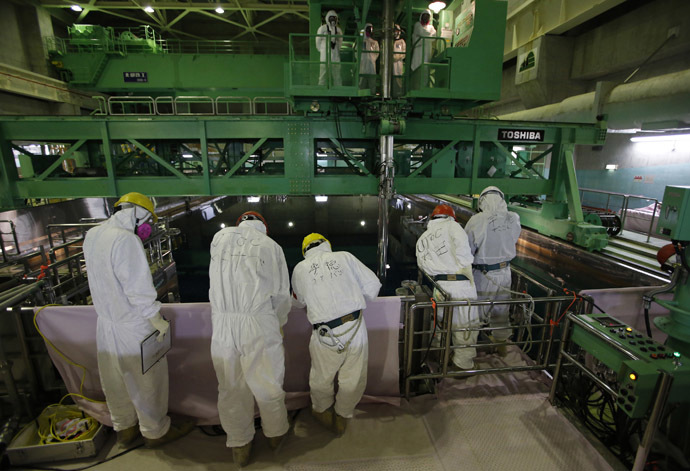 Workers wearing protective suits and masks are seen next to the spent fuel pool inside the Common Pool Building, where all the nuclear fuel rods will be stored for decommissioning, at the Tokyo Electric Power Co (TEPCO) tsunami-crippled Fukushima Daiichi nuclear power plant in the town of Okuma, Fukushima prefecture (AFP Photo/Issei Kato)