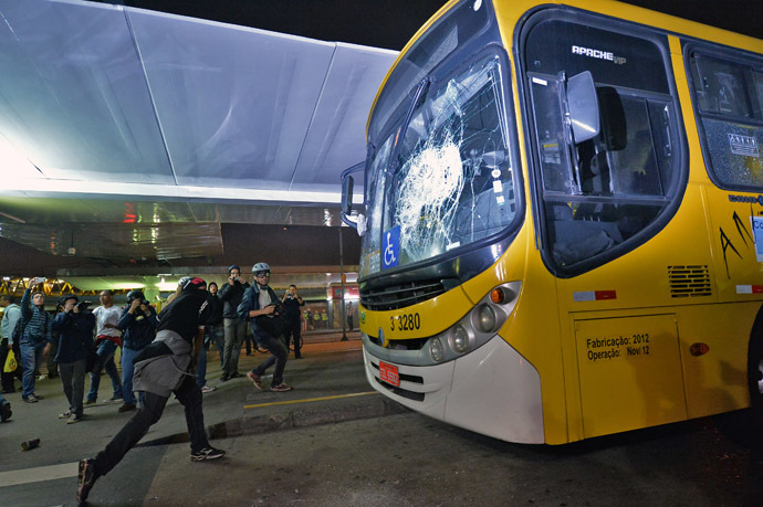 A masked demonstrator throws a stone against a bus after a demonstration against rising public transport costs and demanding better public services in Sao Paulo, Brazil, on October 25, 2013. (AFP Photo/Nelson Almeida)