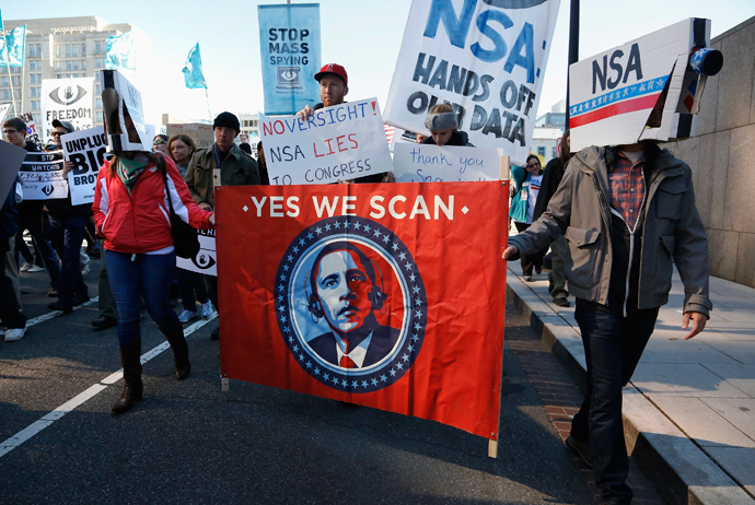 """Demonstrators wearing cardboard surveillance camera hats carry a sign depicting U.S. President Barack Obama at the """"Stop Watching Us: A Rally Against Mass Surveillance"""" march in Washington, October 26, 2013. (Reuters / Jonathan Ernst)"""